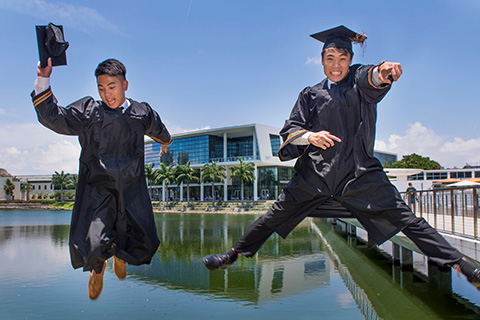 A couple of students celebrating graduation by jumping and posing
