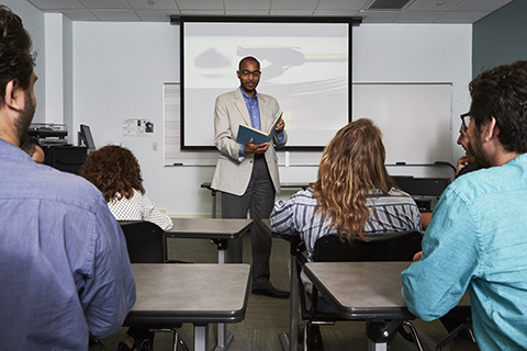 A professor stands at the front of a class with an open book