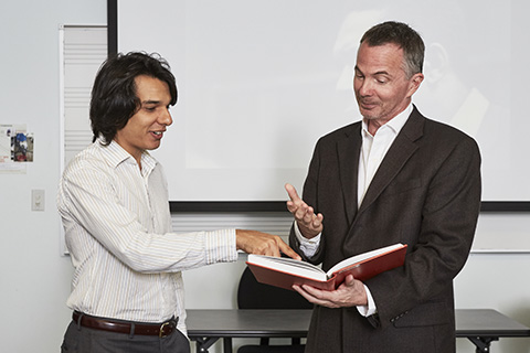 A teacher in a dark suit motions with his hands at  a student in a white dress shirt