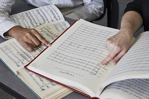 Two hands are pointing at an open book of sheet music