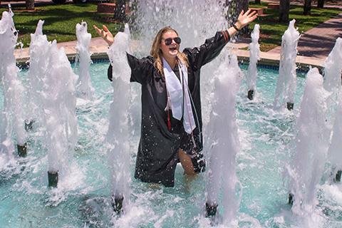 A student celebrates graduation by standing in a fountain